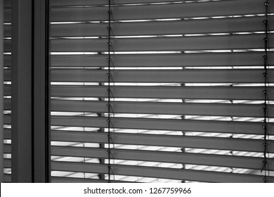 Louvers / jalousie / blinds on windows. Black and white appliance. Abstract background image on the subject of modern architecture or interior.