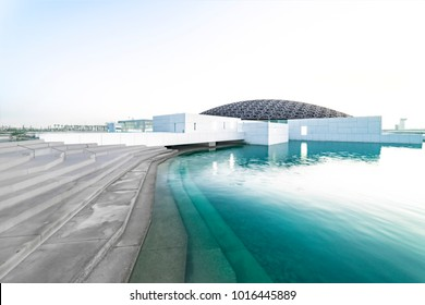 Louvre, Abu Dhabi, United Arab Emirates - Dec.29, 2017: the famous museum of the French architect Jean Nouvel - snow-white boxes under a lace of a dome on turquoise water