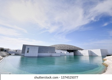 Louvre, Abu Dhabi, United Arab Emirates - Jan.2, 2019: the famous museum of the French architect Jean Nouvel - snow-white boxes under a lace of a dome on turquoise water.