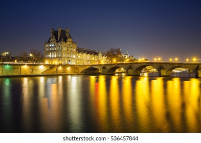 Louvre Museum (Musee du Louvre) and the Royal Bridge (Pont Royal) at night. Louvre museum is one of the world's largest museums with more than 8 million visitors each year.