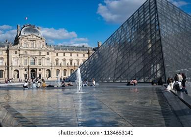 Louvre Museum, Paris France June 2018: Enjoying the summer evening sunshine at the Louvre Museum, Paris, France
