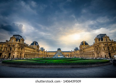 LOUVRE MUSEUM, PARIS, FRANCE - Wide angle shot of Louvre Palace, including famous glass pyramid entrance to art museum, with dramatic clouds in the sky. Iconic, historic landmark/destination