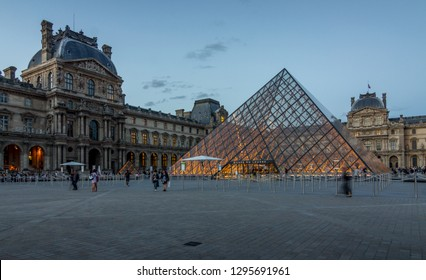 The Louvre museum shows yellow lights through clear glass pyramid. The palace building surrounds the glass pyramid. 9th June 2017, Paris, France.