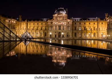 The Louvre in Paris, France shot at night with reflections from the pools