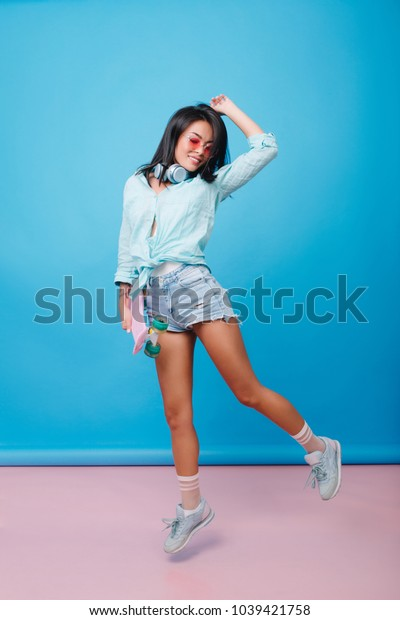 Lovable brunette girl in denim shorts hanging out near blue wall. Sensual hispanic young woman in casual outfit relaxing during indoor photoshoot in studio.