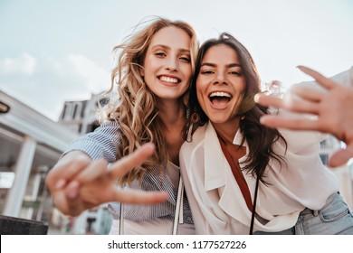 Adorabili ragazze caucasiche che esprimono emozioni positive alla macchina fotografica. Foto all'aperto di raffinate sorelle in posa su sfondo cielo.