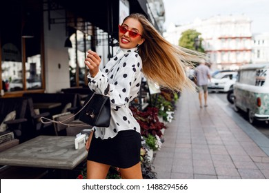 Lovable confident blond woman with long hairstyle posing on the street over modern cafe.  Fashionable look.