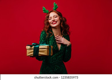 Lovable european girl with christmas present expressing happiness. Refined ginger young woman in green dress laughing on red background in new year.