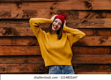 Lovable european girl fooling around during photoshoot on wooden background. Portrait of smiling cheerful woman in red hat and oversize sweater.