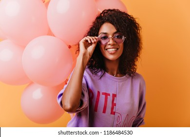 Lovable female model in glasses and purple shirt posing at party. Enthusiastic black young woman having fun during festive.