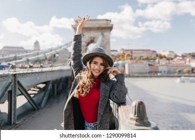 Lovable female tourist in elegant attire expressing happy emotions. Charming white woman in tweed coat exploring city attractions.