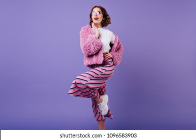 Lovable girl with short hairstyle posing with pleasure in white sneakers in studio. Indoor shot of blissful curly woman in pink fur jacket standing on one leg.