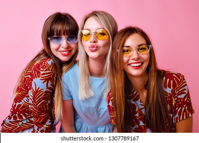 Lovable group of stylish girls smiling and sending kiss on camera, super trendy tropical print clothes and 90s style colorful glasses, best friends enjoy time together, pink background.