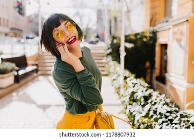 Lovable short-haired girl in yellow sunglasses having fun outdoor and posing with pleasure. Portrait of cute european lady wears green sweater in spring weekend.