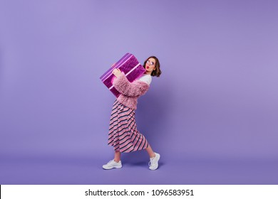 Lovable young woman in white sneakers posing with present box. Studio portrait of fascinating girl making kissing face expressing while holding big gift.