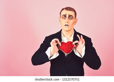 In love again and always. Mime man hold red heart for valentines day. Mime actor with love symbol. Theatre actor pantomime falling in love. Love confession on valentines day.
