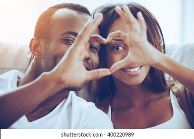Love is in the air! Beautiful young African couple sitting close to each other and looking through a heart shape made with their fingers