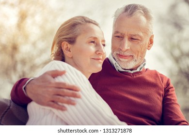 Love in the air. Happy man looking at his wife while spending time together in park