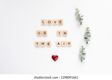 Love is in the air words on white marble background
