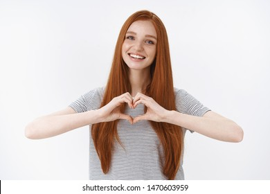Love all you need. Charming romantic charismatic redhead passionate girl blue eyes show heart gesture confessing sympathy look friendly camera smiling, girlfriend express true feelings