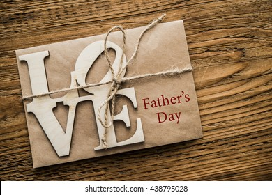 Love alphabet wooden word on brown paper letter. Wooden table background. father's day