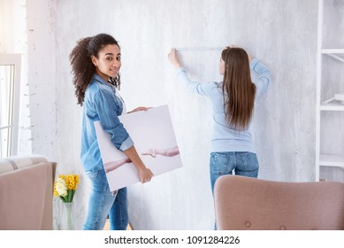 I love art. Beautiful curly-haired girl posing for the camera and holding a picture while her roommate measuring the wall to hang it