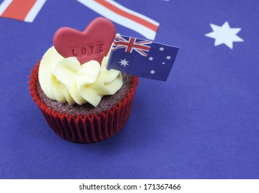 I Love Australia cupcake with love heart and Australian Flag for Australia Day or Anzac Day holidays, against an Australian flag background, with copy space.