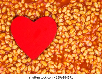 Love for baked beans! Food concept to promote healthy eating. Baked beans background, with room for design / text / copy space, and wooden red heart.