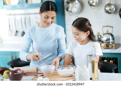 I love baking. Beautiful alert dark-haired young mother beating up some eggs while making some dough and her daughter watching her