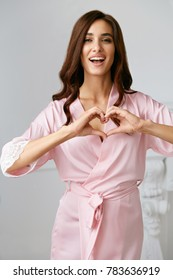 Love. Beautiful Female Model Showing Heart With Hands. Portrait Of Smiling Woman In Silk Pink Fashion Robe With Gorgeous Hair Style And Natural Makeup Making Heart Sign With Hands. High Resolution
