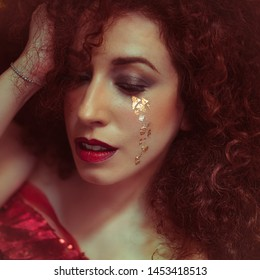 Love, beautiful redhead woman with curly and lush hair with tears of gold leaf in the style of the painter Klimt