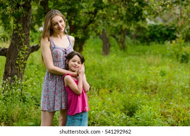 Love between two sister. Caring elder sister embraces the younger one. Young girls of different ages look in the camera with sincere smiles.