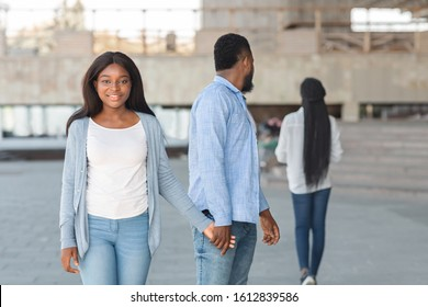 Love is blind. Unfaithful black guy turning head and staring at another woman while walking with his unsuspectful girlfriend, selective focus