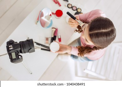 Love blogging. The top view of a cute pretty girl applying powder to her cheekbones while telling her viewers the correct algorithm