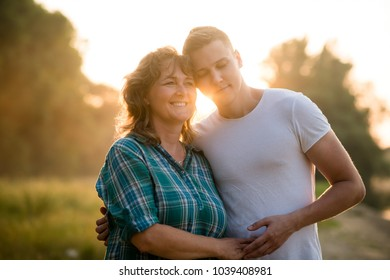 Love bond between son and mother. Sunset background.