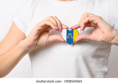 Love Canary Islands. The girl holds a heart in the form of the flag of the Canary Islands on her chest. Concept of patriotism.