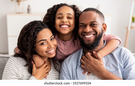 Love And Care. Portrait of cheerful African American family of three people hugging sitting on the sofa at home, posing for photo and looking at camera. Smiling young girl embracing her parents