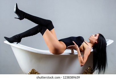 Love and celebrate your amazing body. Care nourish treat body with rich nutritious meals and cosmetic products. Girl slim sexy body lay on bathtub. Erotic woman wear lingerie and high heels relaxing.
