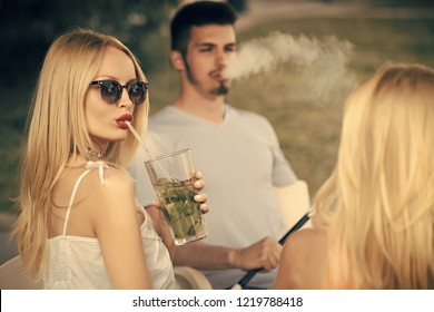 Love, cheating, date, relationship. woman drink mojito cocktail with man. Man vaping hookah pipe with girlfriend in bar. Friends at shisha cafe lounge. Bad habits, party, addiction.