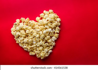 Love Cinema concept of popcorn arranged in a heart shape on red background