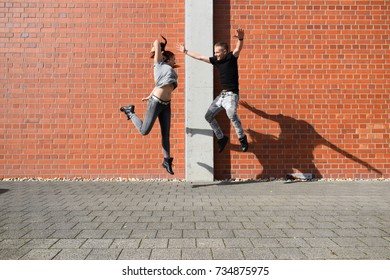 love in the city, urban love, two young people dancing on the street under a red brick wall