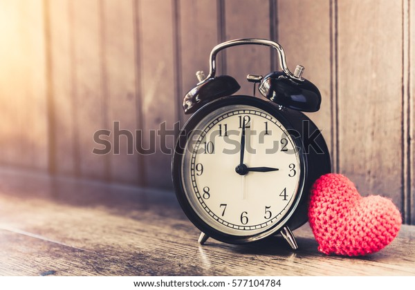 Love clock vintage tone timed 3 o'clock, Time of sweet loving past memories story on the old wood background.