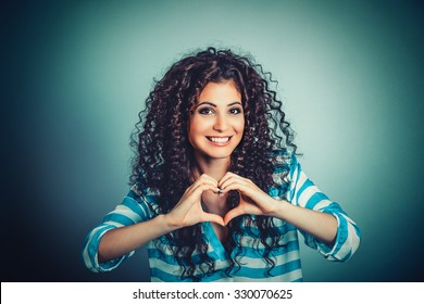 Love. Closeup portrait smiling happy young woman making heart sign, symbol with hands isolated green wall background. Positive human emotion expression feeling life perception attitude body language