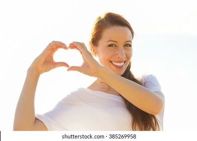 Love. Closeup portrait smiling happy young woman making heart sign, symbol with hands isolated on white background. Positive human emotion expression feeling life perception attitude body language