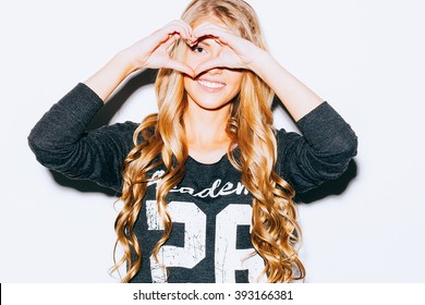 Love. Closeup portrait smiling happy young woman with long blond hair, making heart sign, symbol with hands white wall background. Indoor. Warm color. Hipster.