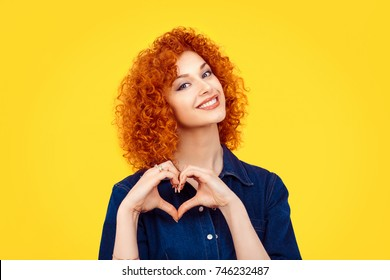 Love. Closeup portrait smiling happy young redhead curly hair woman making heart sign, symbol with hands isolated yellow wall background. Positive human emotion expression feeling life body language