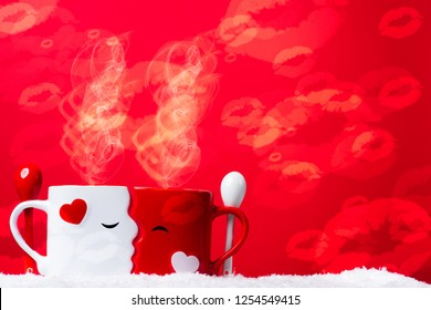 Love at coffe time, valentine's concept, two mugs forming a couple of lovers kissing each other against a red backdrop on a snow bed.