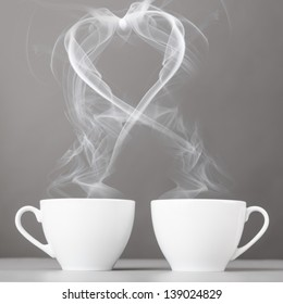 love and coffee. heart silhouette from steaming hot coffee cups