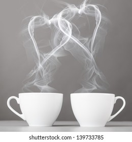 love and coffee. heart silhouettes from steaming hot coffee cups