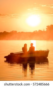 Love and colors of romantic golden river sunset with fog and silhouette of a couple on small boat backlit by sunlight